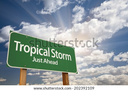 Tropical Storm Green Road Sign with Dramatic Clouds and Sky.