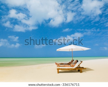 Tropical summer beach holiday couple relax in the sun on their deck chairs  - stock photo