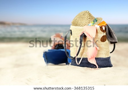 tropical summer day on beach and bag of summer tools