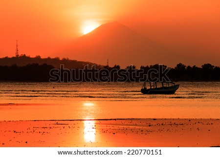 Tropical sun setting behind a large volcano - stock photo