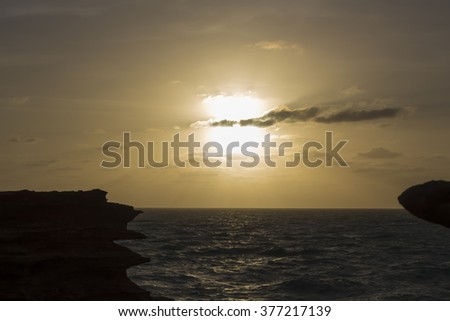 Tropical sun setting  behind  few sparse clouds over the Indian Ocean at Gantheaume Point, Broome, North Western Australia  after a hot humid day  in the summer wet Season. - stock photo