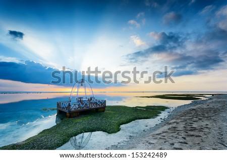 Tropical sunset at low tide. Gili Travangan island, Lombok, Indonesia. - stock photo