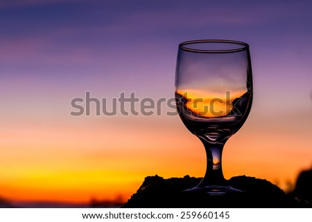 tropical sunset on beach reflected in a wine glass, summertime vacation concept - stock photo
