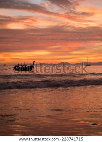 Tropical sunset on the beach with long tailed boats. Ao-Nang. Krabi. Thailand