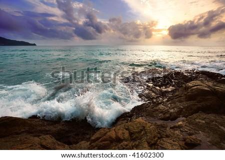 Tropical sunset on the stones beach. Phuket island. Thailand - stock photo