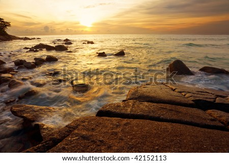 Tropical sunset on the stones beach. Phuket island. Thailand
