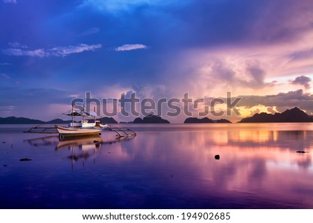 Tropical sunset with a banca boat in El Nido, Palawan - Philippines.  - stock photo