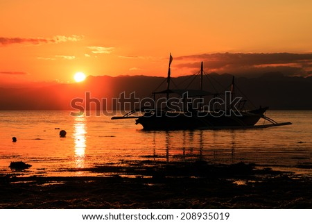 Tropical sunset with traditional boat silhouette on a calm ocean - stock photo