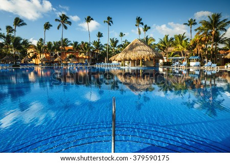 Tropical swimming pool and palm trees in luxury resort - stock photo