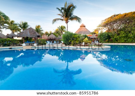Tropical swimming pool at sunrise in Mexico - stock photo