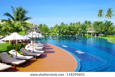tropical swimming pool with coconut tree and white umbrella - stock photo