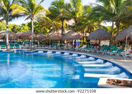 Tropical swimming pool with sunbeds in Mexico - stock photo