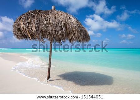 Tropical thatch umbrella on a beautiful Caribbean beach  - stock photo