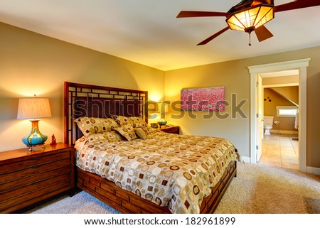 Tropical theme bedroom with queen size bed and nightstands. View of bathroom through the open door.