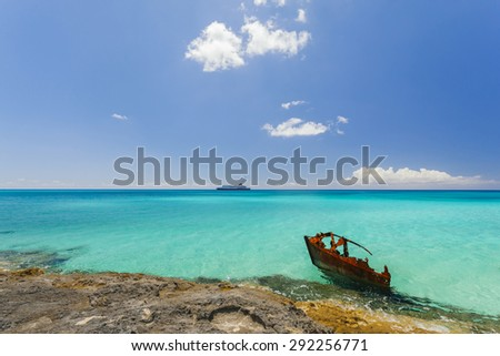 Tropical turquoise clear water with ship wreck and boat on the horizon  - stock photo