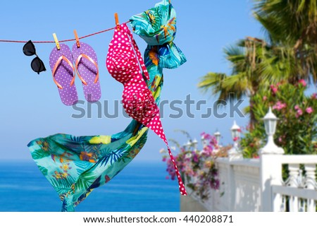 Tropical vacation background with hanging on a rope flip flops, sunglasses and swimsuit - stock photo