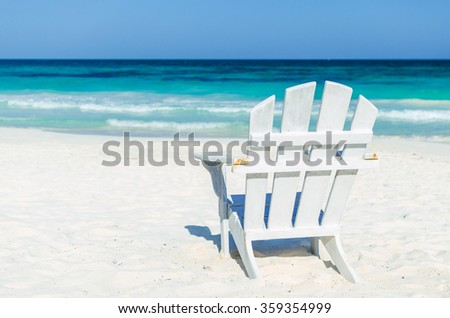 Tropical vacation beach resort sea view. Lonely beach white wooden chair over the background of turquoise sea and blue sky at exotic white sandy beach in the Caribbean sea - stock photo
