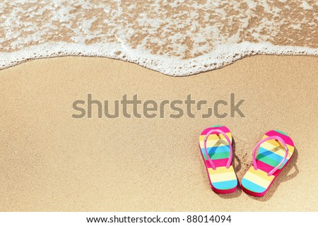 Tropical vacation concept--Flipflops on a sandy ocean beach - stock photo