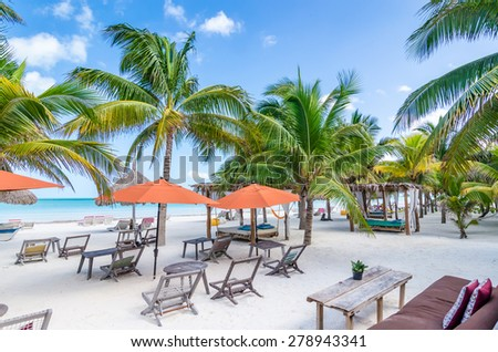 Tropical vacation resort summer view through palm trees with beautiful colourful decor, beach tables, lounges and wooden chairs at exotic white sandy beach in the Caribbean sea, Holbox island, Mexico