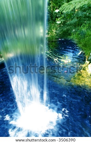 tropical waterfall with smooth edge and yellow and red flowers in the background of a garden view