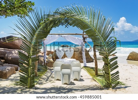 Tropical wedding setting on sandy beach in front of blue ocean. Beautifully decorated scene with green palm leaves, chairs and table