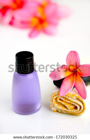 Tropical wellness spa & aromatherapy concept with plumeria flower and stones, isolated on white background
