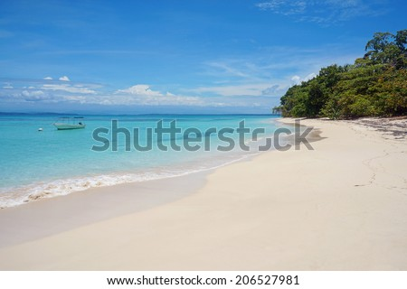 tropical white sand beach with turquoise water and a boat on mooring buoy, Caribbean sea, Zapatilla islands, Panama - stock photo