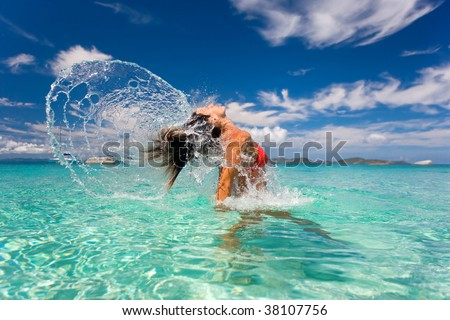 tropical woman flips hair in turquoise waters - stock photo