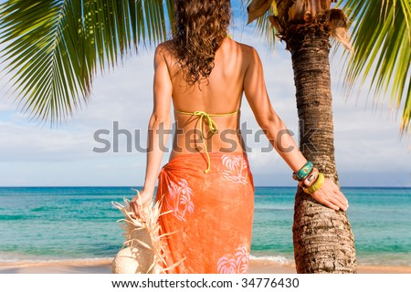 tropical woman on hawaii beach with blue water - stock photo