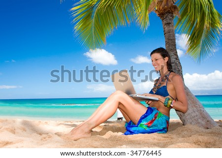 tropical woman on hawaii beach with blue water with laptop