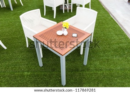 Tropical wooden dinning table on green grass with reserve sign on the table, taken on a cloudy day