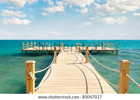 tropical wooden pier in turquoise sea at sunny weather, cloudy skies