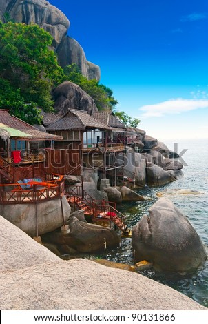 Tropical wooden villas on the rocks of a bay - stock photo
