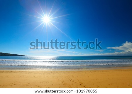 Tropical yellow beach blue clear sky with sun and sea - stock photo