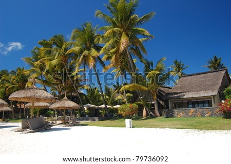 Trou Aux Biches sandy beach with palm trees and bungalows on Mauritius island - stock photo