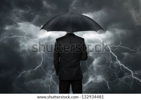 Trouble ahead, businessman with umbrella standing in front of a stormy sky - stock photo