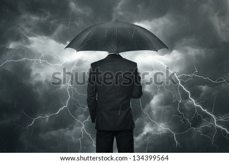 Trouble ahead concept, businessman with umbrella standing in the rain