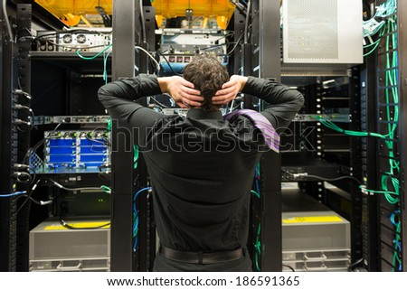 Trouble in data center. Man looking astonished in a network data center.   - stock photo