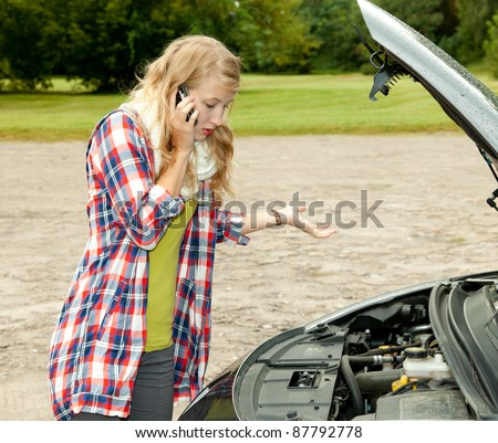 trouble with the car engine in the road, young woman phoning to help - stock photo
