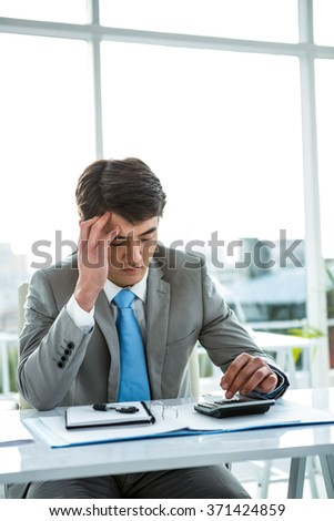Troubled asian businessman using calculator in his office