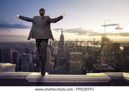 Troubled businessman jumping from the top of a building - stock photo