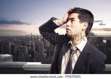 Troubled businessman on top of a building - stock photo