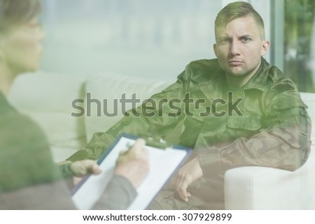 Troubled soldier during psychotherapy session at psychiatrist's office - stock photo