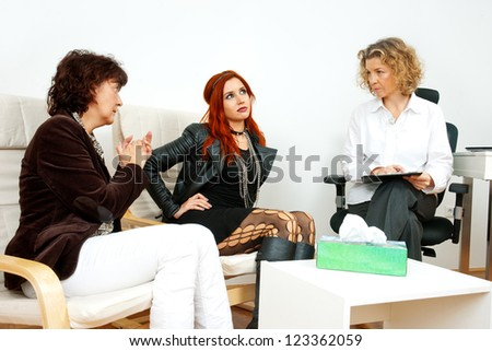 troubled teen girl on therapy session with her mother and psychiatrist