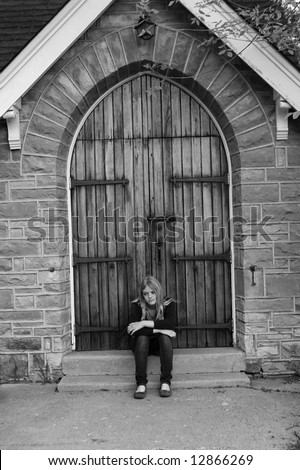 Troubled teen sits on church steps looking for help. - stock photo