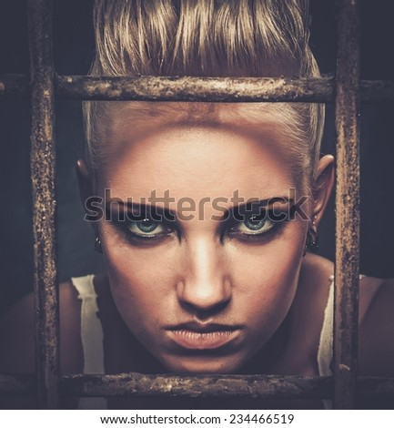 Troubled teenager girl behind bars - stock photo