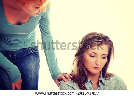 Troubled young girl comforted by her friend.