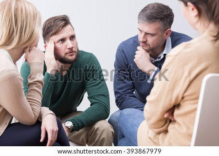 Troubled young man confiding to his supporting psychotherapy group - stock photo
