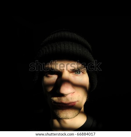 Troubled youth or some sort of creepy talker criminal in the dark black shadows staring out the his window or jail cell. - stock photo