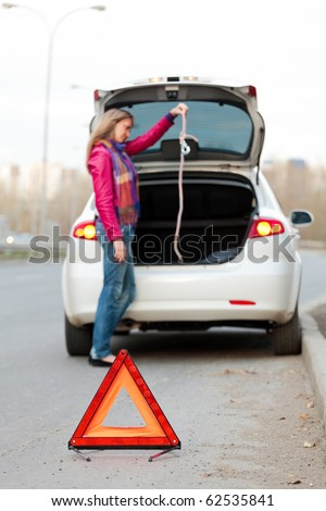 Troubles on the road. Focus is on the red triangle sign. - stock photo